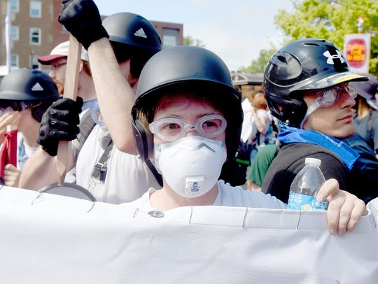 A counter protester wears goggles, breathing mask,