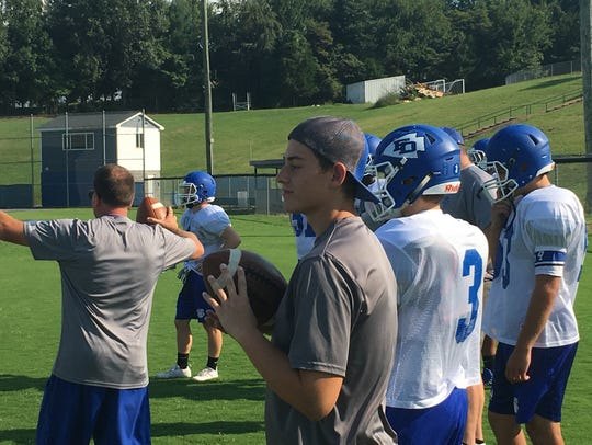 Sam Hill (center) watches practice Monday, Aug. 21.