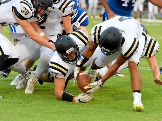 Buffalo Gap's Seth Fitzgerald dives after a football fumbled by Fort Defiance as teammate Jay Johnson scoops the ball up and will run it for several yards for a game turnover during a football game played in Fort Defiance on Friday, August 25, 2017.