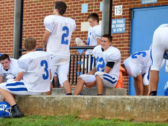 Fort Defiance's Aaron Wright (center) smiles as he sits among teammates after practice ends at the school on August 9, 2017.