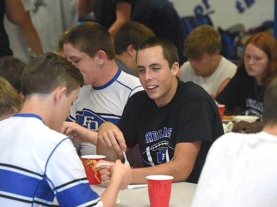 Fort Defiance junior wide receiver Bryce Owens sits and eats with teammates at a pre-game dinner before their evening's home game at the school on August 25, 2017.