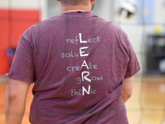 Coach Jonathan Frame has LEARN on the back of his shirt as he works with his players at the start of team practice at Shelburne Middle School on Tuesday, Aug. 29, 2017. Each letter has a word associated with it: reflect, solve, create, grow and think.