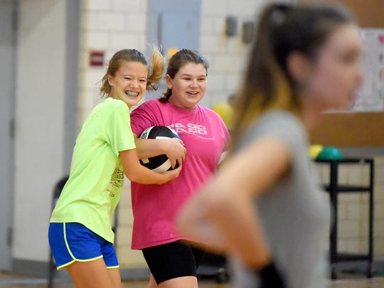 Seventh-grader Hannah Ashworth laughs as she tries to take a volleyball from teammate Ellie Lockridge, also seventh-grade, during practice at Shelburne Middle School on Tuesday, Aug. 29, 2017.
