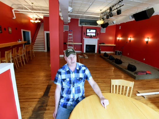 A musician himself, owner Mark Smith sits with the new stage area behind him as he transforms the restaurant space into the soon-to-open Acoustic Taphouse in downtown Staunton.