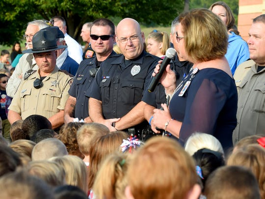 "Law enforcement officers listen as principal Fonda Morris addresses those gathered out front of Clymore Elementary. Students at the school invited first responders, active military and veterans to join them and students from Fort Defiance High School and Stewart Middle to honor them for the school's annual ""National Anthem Day"" on Sept. 11, 2017."