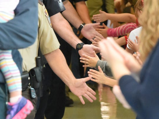 "First responders, active military and veterans walk through the halls of Clymore Elementary to the sound of applause as they touch hands with the students and faculty gathered to either side of the hallway. Clymore Elementary held its annual ""National Anthem Day"" on Sept. 11, 2017."