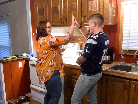 Sage Fisher (right) slaps hands with friend Callie McAllister who just successfully administered his weekly injection of testosterone at his home in Crimora on Sept. 7, 2017. Fisher has been inviting friends and family to give him his weekly shot and posting images and video on Facebook and Instagram as part of documenting his transition.