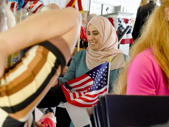 Ghufran Abdulsalam Al Saadoon smiles as she receives a small American flag as a gift after stepping off the stage with her certificate of naturalization in hand. America got more than 70 new citizens at a naturalization ceremony held at the Frontier Culture Museum on Tuesday, Sept. 19, 2017.