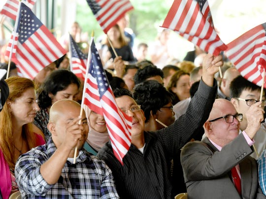 Jose Antonio Padilla Jovel (center) waves his flag with enthusiasm between fellow petitioners Ever Augusto Calderon Aguilar and Rolando Melquiades Heredero Lastra  after they are officially called U.S. citizens.  America got more than 70 new citizens at a naturalization ceremony held at the Frontier Culture Museum on Tuesday, Sept. 19, 2017.