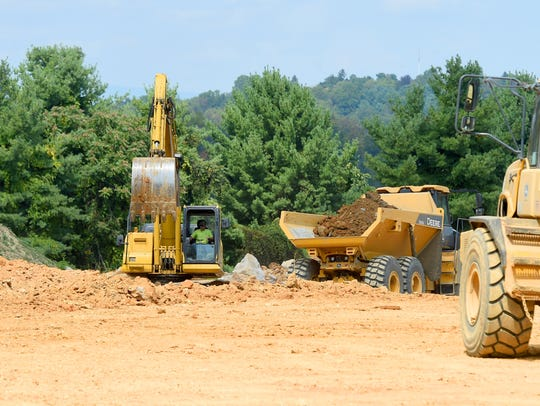 An excavator helps work land being developed for a