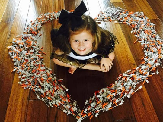 Aida Aleshire, 6, sits in the middle of a year's worth of insulin needles the first-grader uses to regulate her Type 1 diabetes.