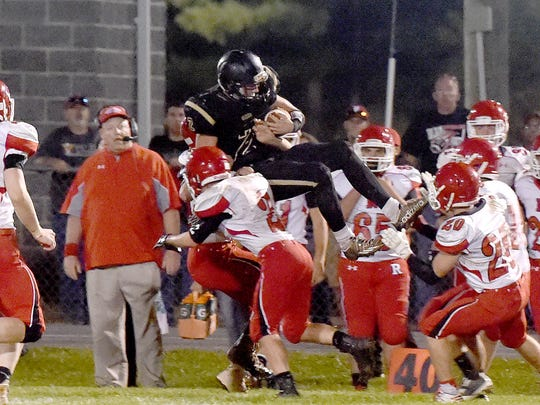 Buffalo Gap's Dylan Rankin goes high with the ball, his legs kicked out in front of him as he is grabbed from behind by Riverheads' defenders during a football game played in Swoope on Friday, Sept. 22, 2017.