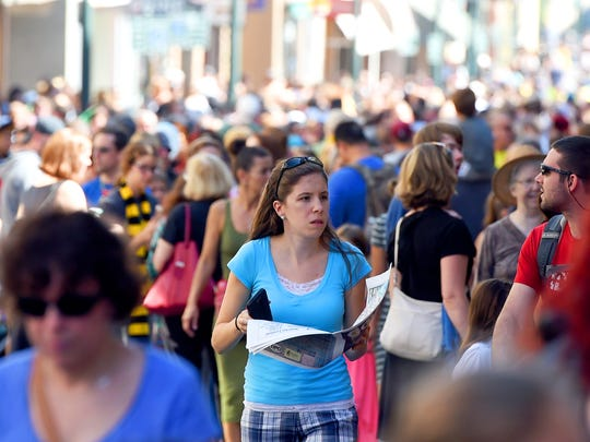 A lady refers to the festival map while walking among the crowd along West Beverley Street during the Queen City Mischief & Magic festival in downtown Staunton on Saturday, Sept. 23, 2017. The three-day festival celebrating Harry Potter ends Sunday, Sept. 24, 2017.