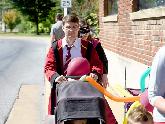 A festival-goer is dressed as an older Harry Potter as he pushes a baby carriage during the Queen City Mischief & Magic festival in downtown Staunton on Saturday, Sept. 23, 2017. The three-day festival celebrating Harry Potter ends Sunday, Sept. 24, 2017.