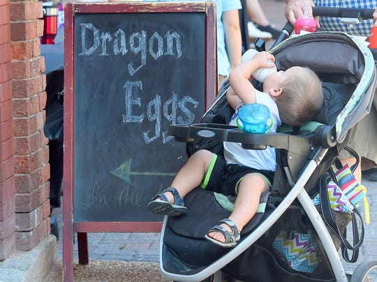 Dragon Eggs can be found at the business where a young hatchling passes by in a baby carriage during the Queen City Mischief & Magic festival in downtown Staunton on Saturday, Sept. 23, 2017. The three-day festival celebrating Harry Potter ends Sunday, Sept. 24, 2017.