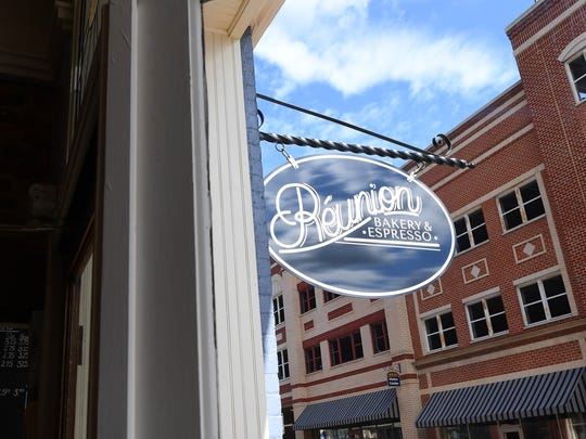 Sign hangs in front of Réunion Bakery & Espresso, marking its location at 26 South New Street in downtown Staunton.