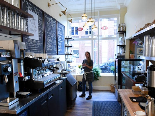 Manager Amanda Green stands with coffee in hand near the serving window inside Réunion Bakery & Espresso located at 26 South New Street in downtown Staunton.