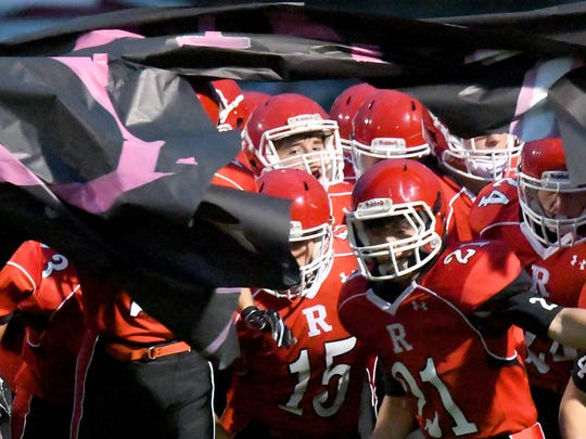 The Riverheads' varsity football team breaks through the banner and takes the field for a football game played in Greenville on Friday, Oct. 13, 2017.