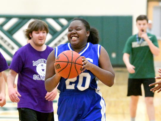 R.E. Lee's Toneya Shaw smiles big as she has the ball during one of two Unified Basketball finale games played in Fishersville on Monday, Oct. 16, 2017.