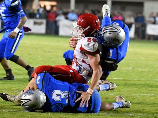 RIverheads' Dalton Jordan is tripped up and brought down by Robert E. Lee's Jayden Williams and Ta'Corrious Strother during a football game played in Staunton on Friday, Oct. 20, 2017.