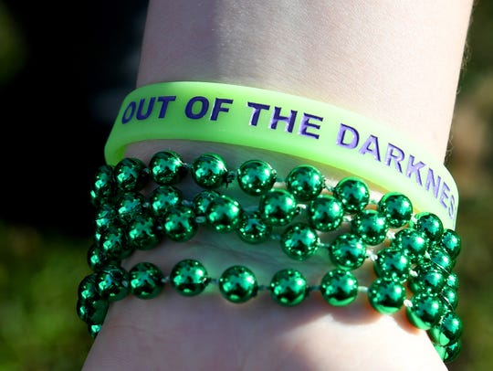 """Beads and an """"Out of the Darkness"""" bracelet worn by"""