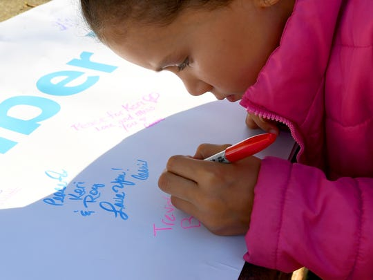 "Imani Banks, 7, of Harrisonburg writes a personal message to a loved one on the ""We Remember Them"" banner. The third annual Greater Augusta Out of the Darkness Walk was held at Gypsy Hill Park on Saturday, Oct. 21, 2017. The event brought together people affected by suicide and promoted awareness to suicide prevention."