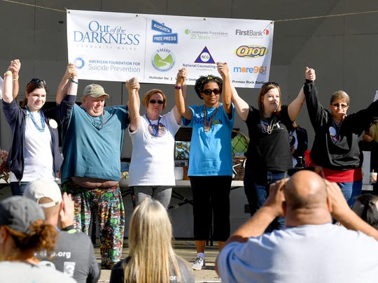 Participants on stage who were recognized as having lost loved ones to suicide raise their hands as one during the honor bead ceremony. The third annual Greater Augusta Out of the Darkness Walk was held at Gypsy Hill Park on Saturday, Oct. 21, 2017. The event brought together people affected by suicide and promoted awareness to suicide prevention.