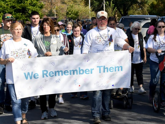 "Ginger and Mark Ham of Staunton hold the ""We Remember Them"" banner and lead the way. Participants walk three laps together around Gypsy Hill Park as part of the third annual Greater Augusta Out of the Darkness Walk on Saturday, Oct. 21, 2017. The event brought together people affected by suicide and promoted awareness to suicide prevention."