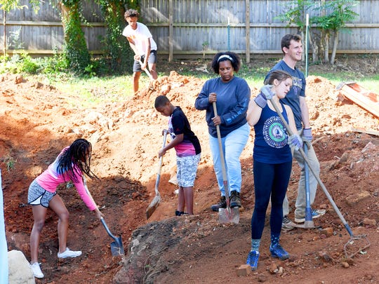 A partner family, Very Brown (center) works with daughter Emysja Caul (left), 13; son Kyiam Brown, 15; and son Ajablea Caul, 11. They join volunteers in shoveling dirt from a pile back into place around the house being renovated by Staunton-Augusta-Waynesboro Habitat for Humanity for her family on Saturday, Oct. 21, 2017.