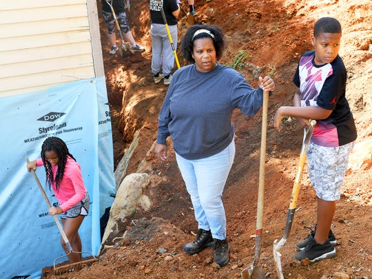 Very Brown, a partner family member, works alongside her children and volunteers. They shovel dirt from a pile back into place around the house being renovated by Staunton-Augusta-Waynesboro Habitat for Humanity for her family on Saturday, Oct. 21, 2017. She stands between 13-year-old daughter Emysja Caul and 11-year-old son Ajablea Caul.