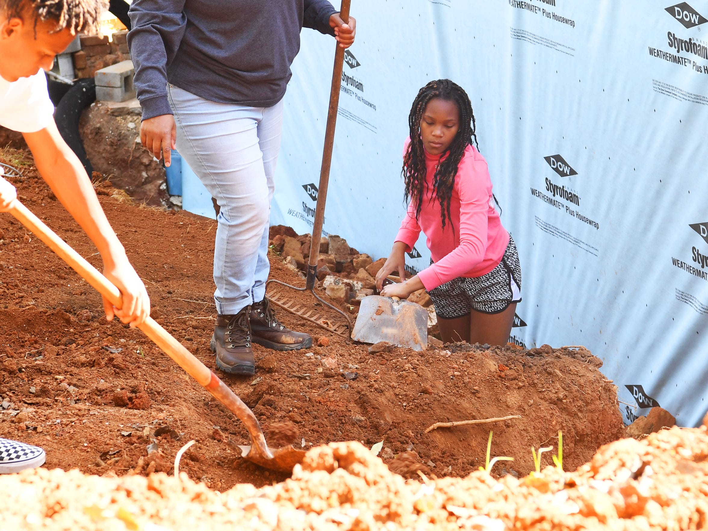 Thirteen-year-old Emysja Caul, a partner family member, works alongside her mother and brothers. They shovel dirt from a pile back into place around the house being renovated by Staunton-Augusta-Waynesboro Habitat for Humanity for her family on Saturday, Oct. 21, 2017. She works between 15-year-old son Kyiam Brown, 15, and 13-year-old daughter Emysja Caul.