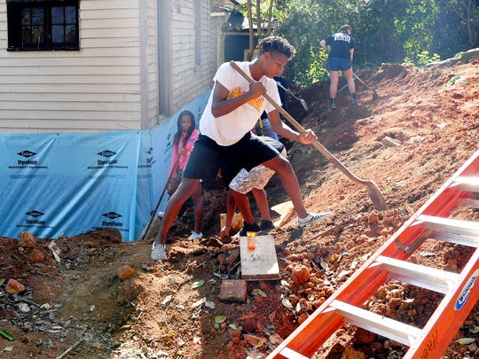 Fifteen-year-old Kyiam Brown, a partner family member, works alongside his mother, brother and sister. They shovel dirt from a pile back into place around the house being renovated by Staunton-Augusta-Waynesboro Habitat for Humanity for her family on Saturday, Oct. 21, 2017. She works between 15-year-old son Kyiam Brown, 15, and 13-year-old daughter Emysja Caul.