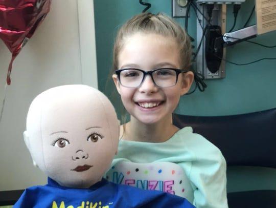 McKenzie Woods, 8, holds a MediKin doll named Logan