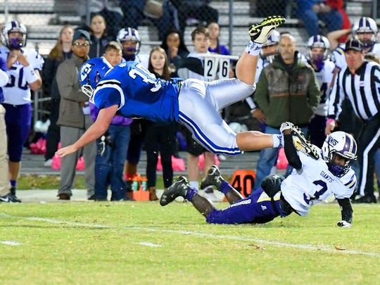 Fort Defiance's Tristen Simmons has the ball as he flies overtop Waynesboro's Dayvon Young who still has a hold on Simmons' ankle for a tackle during a game played in Fort Defiance on Friday, Oct. 27, 2017.
