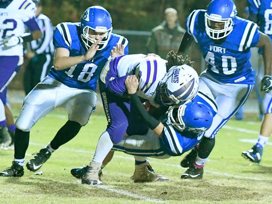 Waynesboro's Alijah Braxton is tackled by Fort Defiance's Dillon Stickley and Addison Nicely with Treason Winston looking to get in on the tackle during a game played in Fort Defiance on Friday, Oct. 27, 2017.