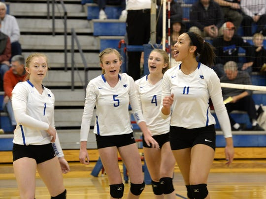 Jayden Beasley (11) celebrates a kill with teammates Tori Cleveland (4), Madison Painter (5) and Madi Kimmel (1) Monday night in a win over Turner Ashby.