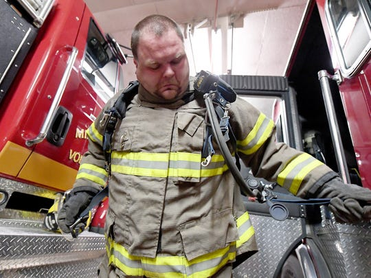 Volunteer firefighter Frank Dull slips on an air pack as he talks about the various gear worn and used by firefighters during an interview at the firehouse for the Middlebrook Volunteer Fire Department on Oct. 23, 2017.