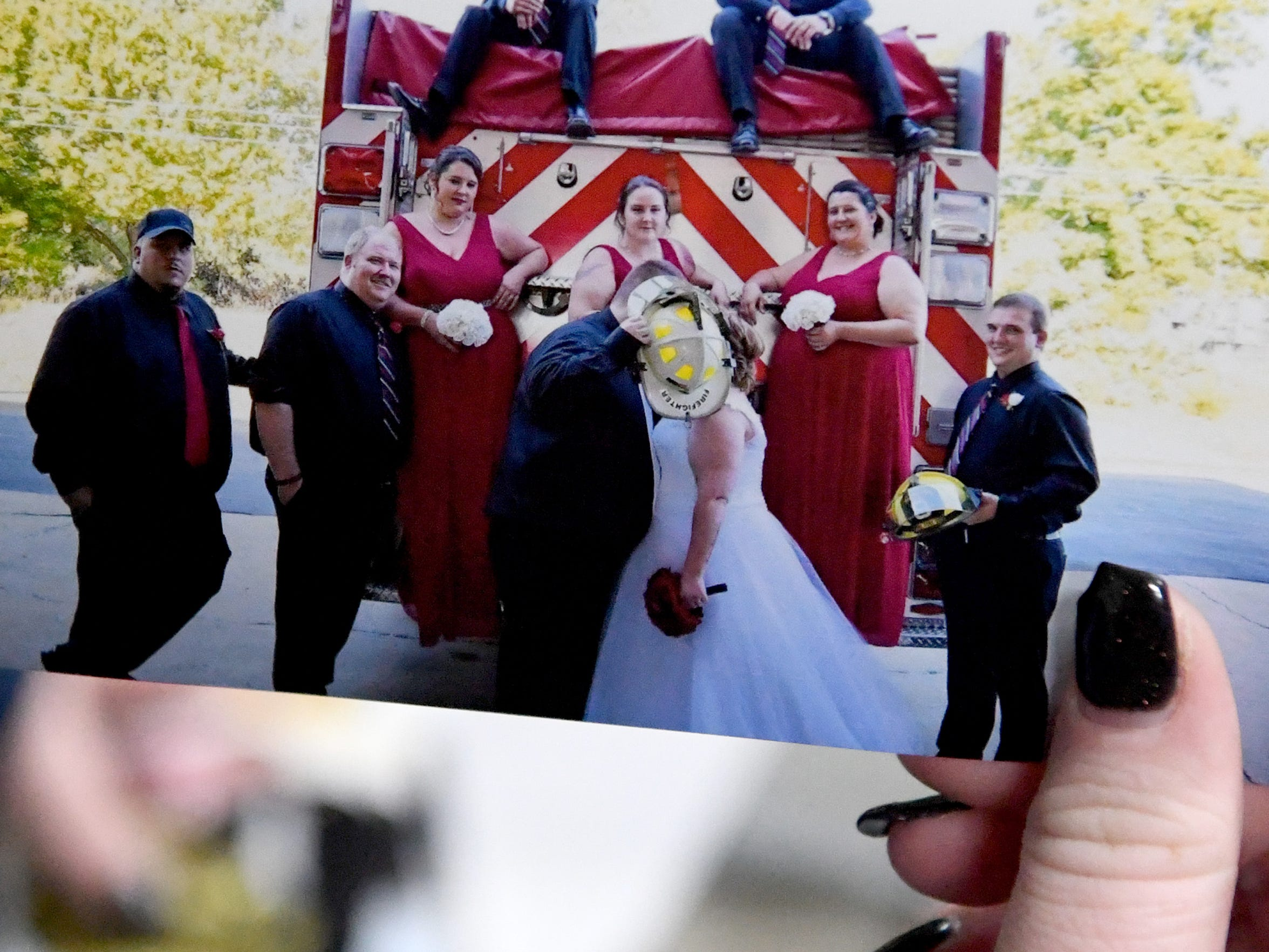A photo of groom and assistant chief Timmy Anderson kissing new wife MacKenzee Anderson, volunteer EMT / secretary, behind a fire helmet. The two were married at Dooms Volunteer Fire Company's firehouse where they both volunteer.