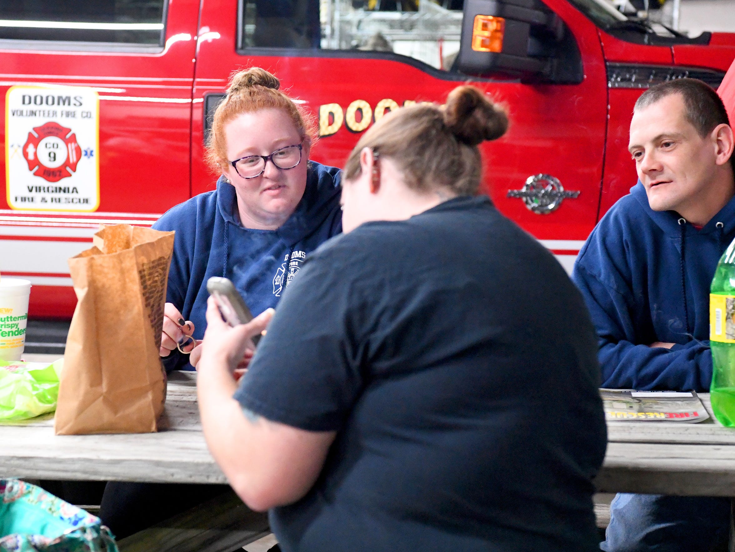 Dooms volunteers MacKenzee Anderson, Michael Hartsook and Tiffany Bright hang out at the firehouse on a Thursday night in October, ready in case any calls come in. Bright enjoys this downtime to socialize with the other volunteers there who are some of her best friends.