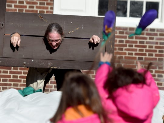 """George Platts, portraying a person from the colonial period locked in a pillory, gets """"rotten fruit and vegetables"""" thrown at him by twin sisters Madeline and Isabella Fedor, 6, of York City."""