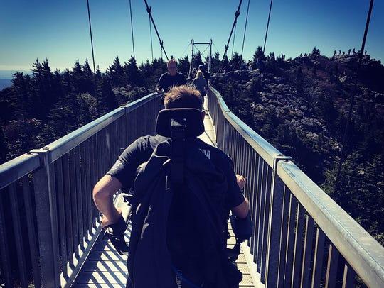 Photo of Rob Corbett crossing a mile-high swinging