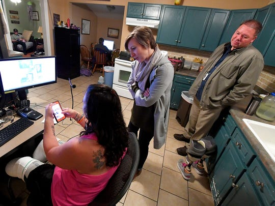 Vocational therapist Samantha Weaver and assistive technology specialist Tim Bobsin of Wilson Workforce and Rehabilitation Center observe as Cortney Small uses both cellphone and computer during a home visit in Crimora on Nov. 12, 2017.  The computer system and workspace have been tailored to help with Cortney with her work, despite her loss of several fingers and legs below the knees.