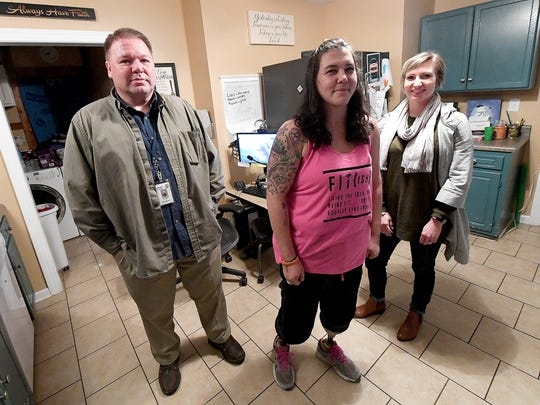Assistive technology specialist Tim Bobsin and vocational therapist Samantha Weaver of Wilson Workforce and Rehabilitation Center are part of the team with Wilson Workforce and Rehabilitation Center who have been assisting Cortney Small (center) in her recovery. They are photographed in Cortney's home in Crimora on Nov. 12, 2017.