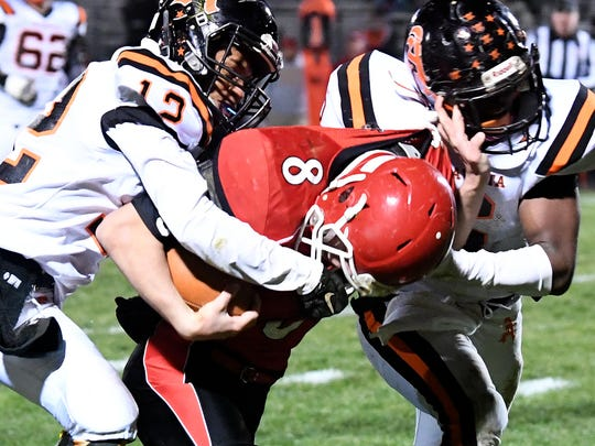 Riverheads' Zac Smiley's head is pulled down after Altavista's Jonta Goard grabs his face mask during a Region 1B semifinal game played in Greenville on Friday, Nov. 17, 2017.