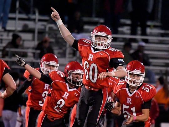 Riverheads' Bryan Hostetler goes highest as he joins teammates in signaling a turnover after they intercept an Altavista pass during a Region 1B semifinal game played in Greenville on Friday, Nov. 17, 2017.