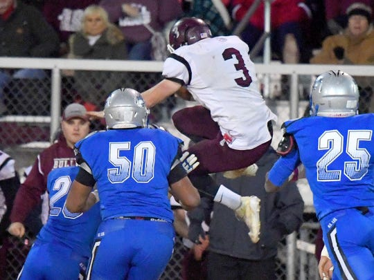 Luray's Dylan Jenkins jumps high with the ball as he tries to vault a Robert E. Lee player trying to make the stop during the Region 2B championship football game played in Staunton on Friday, Nov. 24, 2017.