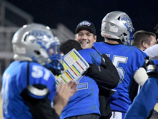 Robert E. Lee head coach Scott Girolmo is hugged by