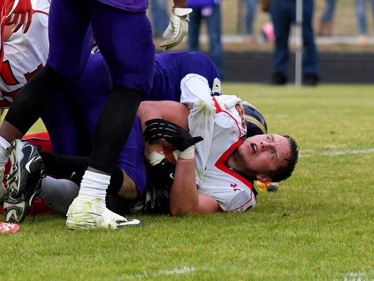 A Riverheads' player loses his helmet after being brought