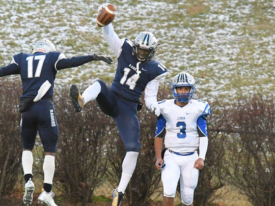 Robert E. Lee's Jayden Williams stands still as Appomattox County's Collen Shaw and DeÕVon Graves celebrate a touchdown during the VHSL Class 2 state championship in Salem on Sunday, Dec. 10, 2017.