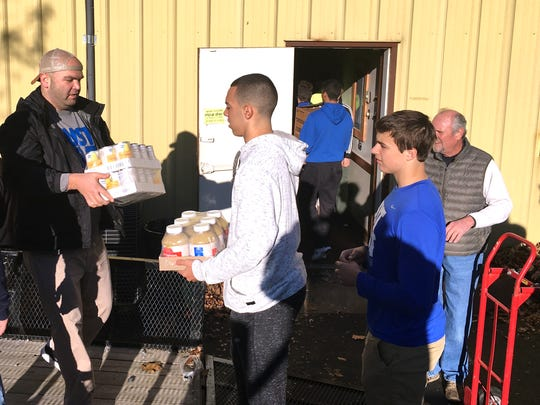 Lee High seniors Tre Simmons and Everett Castle wait to carry boxes of food into the Staunton Elks Lodge. The food and other items were distributed to families in need Saturday afternoon.